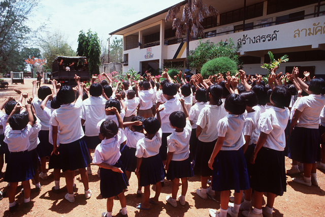 Students at the Ban Laem Ruek Elementary School wave goodbye to members of the 84th Engineering Battalion after the dedication ceremony for the newly renovated community hall. The building was renovated as part of a civic action program during the joint Thai-U.S. training exercise Cobra Gold '92