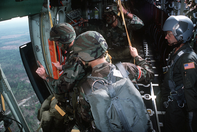 TECH. SGT. Michael Schoenberger, loadmaster with the 179th Airlift Group, Ohio Air National Guard, assists a jump master from the Army's XVIII Airborne Corps as troops prepare to parachute from a C-130 Hercules aircraft during a training exercise