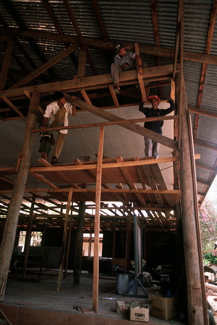 Thai civilians work on the rafters of the Ban Laem Ruek community hall. The renovation of the building is being conducted as part of a civic action program during the joint Thai-U.S. training exercise Cobra Gold '92