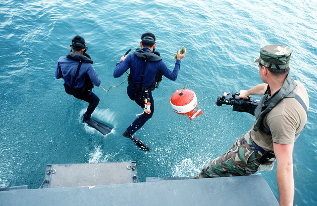 While STAFF SGT. Kevin Schwandt, a combat camera videographer watches, a pair of Royal Thai Navy special forces troops jump into the water from a boat during the joint Thai-U.S. training exercise Cobra Gold '92. They are participating in a simulated mine attack on a ship at the Sattahip Royal Thai Navy Base