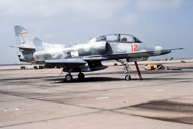 A right side view of a Fighter Squadron 126 (VF-) TA-4J Skyhawk aircraft parked on the flight line and exhibiting the fin flash of China to represent an aggressor country. The aircraft is providing adversary training for Pacific Fleet-based squadrons