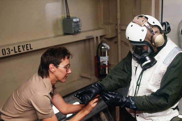An ensign aboard the Military Sealift Command hospital ship USNS MERCY (T-AH-19) assists an external litter bearer with his Chemical, Biological and Radiological (CBR) clothing and a MCU-2P gas mask in a mass casualty exercise during Operation Desert Shield