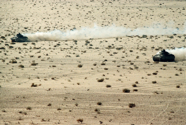 Two M-2 Bradley infantry fighting vehicles maneuver in the desert during a U.S. and Saudi live-fire exercise during Operation Desert Shield