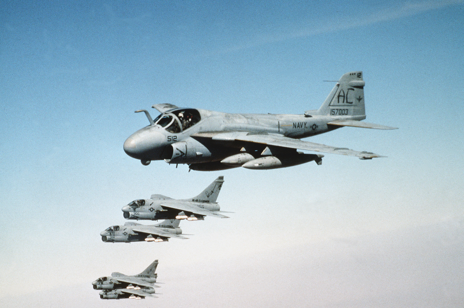 An A-6E Intruder aircraft and Attack Squadron 46 (VA-46) A-7E Corsair II aircraft fly in formation as they prepare for refueling during Operation Desert Storm. The Corsairs are armed with cluster bombs.