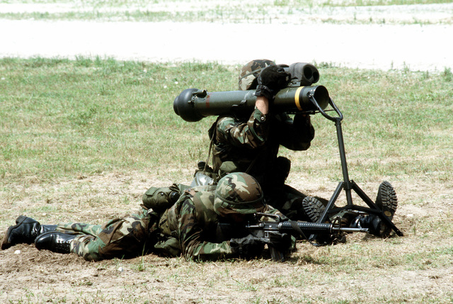 While sitting in the ready to fire position, a combat infantry Marine gazes through the tracker assembly of an M-47 Dragon medium anti-tank assault weapon. He is accompanied by a fellow Marine rifleman lying in the prone position and armed with an M-16A2 rifle
