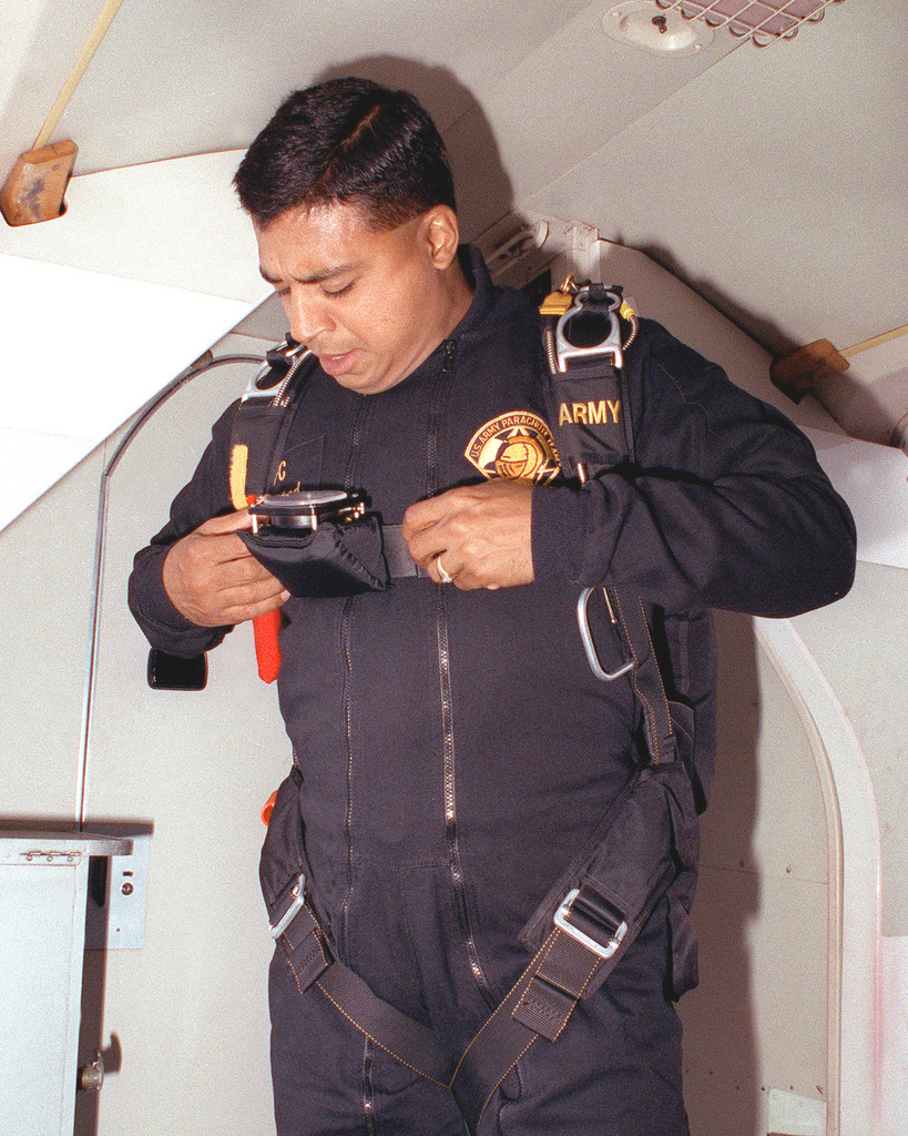 A member of the U.S. Army Golden Knights parachute team checks his equipment