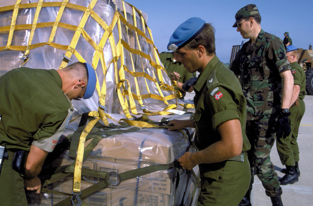 Norwegian United Nations forces personnel and a member of the 4th Mobile Aerial Port Squadron break down pallets containing 50,000 read-to-eat meals (MREs). Two C-141B Starlifter aircraft, one from the 437th Airlift Wing of Charleston Air Force Base, S.C., and another from the 63rd Airlift Wing of Norton Air Force Base, Calif., delivered the MREs to war-ravaged Croatia.