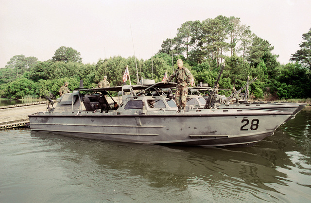 U.S. Marine Corps riverine assault craft RAC-28 and two other RACs are docked at a pier during a joint military training exercise called Ocean Venture '92. Each RAC, used for drug interdiction and troop and fire support, has a Mark 19 40mm grenade launcher in the back and an M-2 .50-caliber machine gun mounted on the front