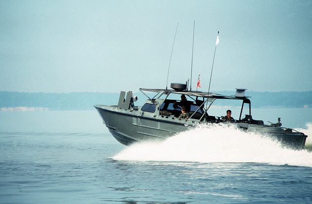 U.S. Marine Corps riverine assault craft RAC-55 patrols by the beach during a joint military training exercise called Ocean Venture '92. The RAC, used for drug interdiction and troop and fire support, has a Mark 19 40mm grenade launcher in the back and an M-2 .50-caliber machine gun mounted on the front