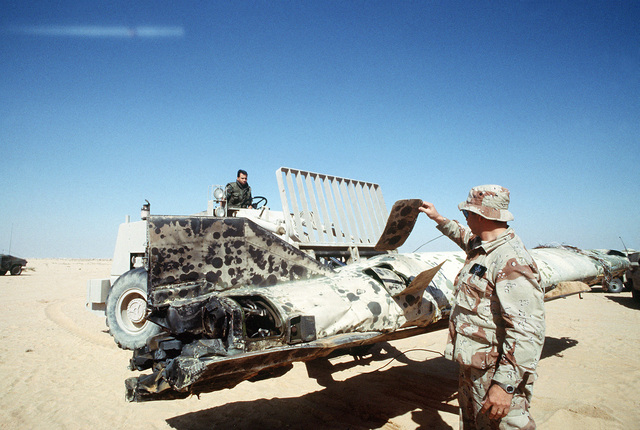 SENIOR MASTER SGT. James Miles of the 4409th Explosive Ordnance Disposal Branch, Myrtle Beach, S.C., examines the remains of a Scud missile shot down by an MIM-104 Patriot tactical air defense missile outside of Riyadh during Operation Desert Storm. STAFF SGT. Stephen Olava of the 347th Transportation Squadron, Moody Air Force Base, Ga., operates an M-13K rough terrain fork lift truck to transfer the missile to a flatbed trailer