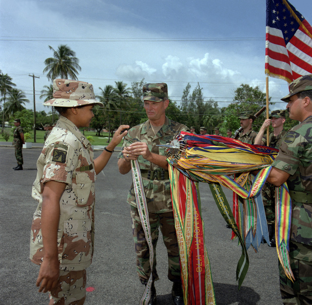SPECIALIST DeJesus, a member of the Puerto Rico Army National Guard, presents the Defense of Saudi Arabia streamer to COL Emmette Y. Burton during the Armed Forces Day celebration at Headquarters, Fort Buchanan. DeJesus was among the first women to be deployed to the Persian Gulf during Operations Desert Shield/Desert Storm