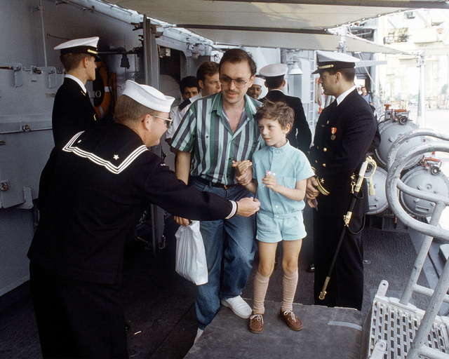 A member of the quarterdeck watch on the guided missile frigate USS HAWES (FFG-53) gives a boy a lollipop before he leaves the ship. The HAWES also visited ports in Estonia and Lithuania after participating in BALTOPS '92. This was the first visit to these countries by a U.S. ship since 1924
