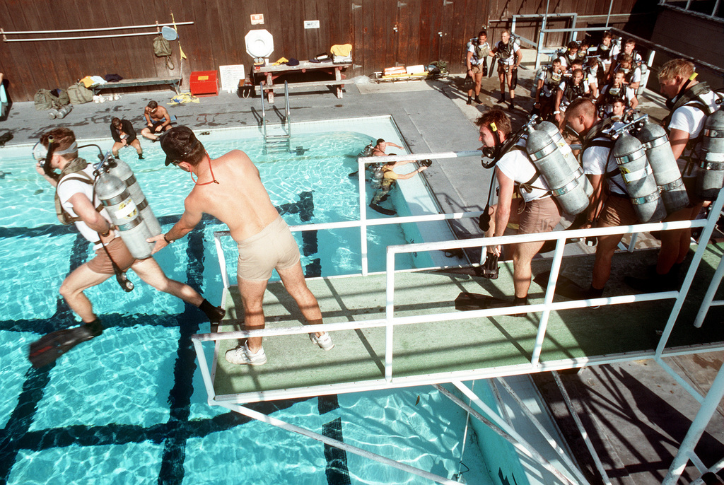 A scuba gear clad student in a second class diver course jumps from a platform into a pool