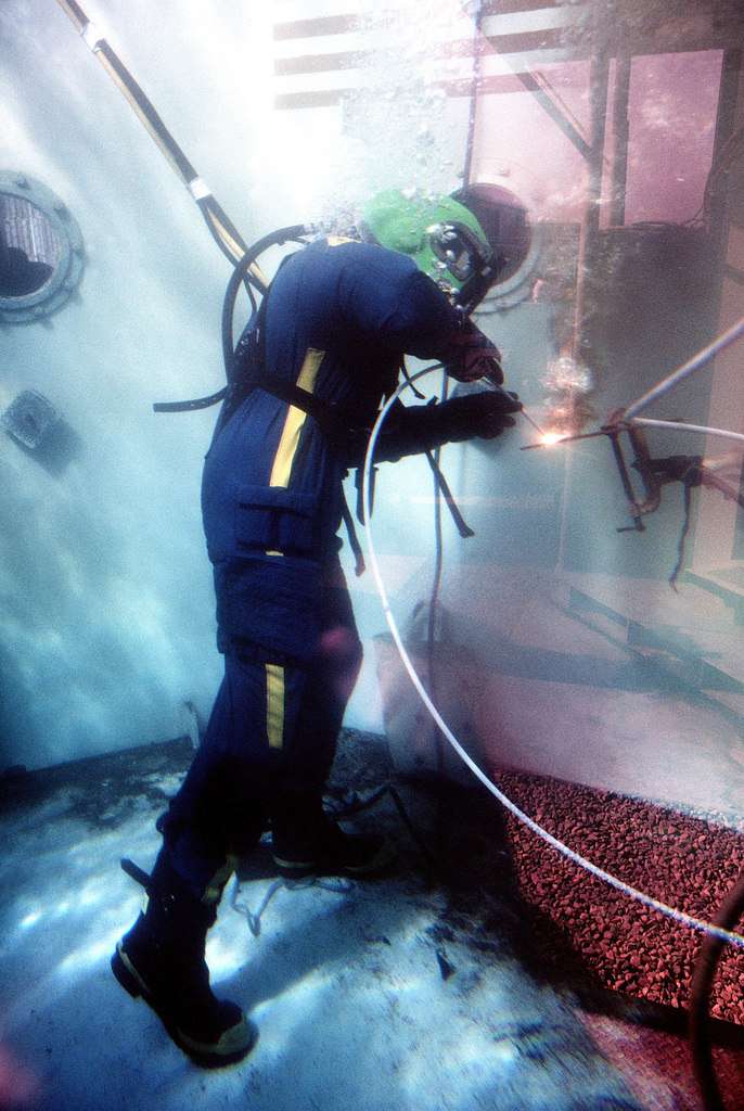 A student in a second class diver course uses a torch in an underwater tools instruction tank. The student is wearing Mark 12 diving gear