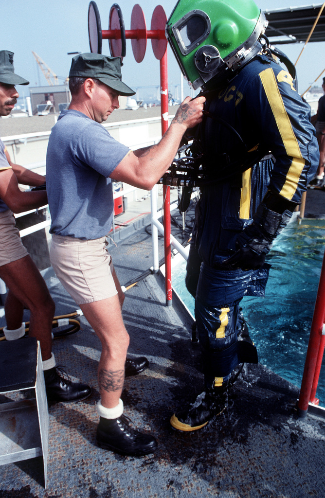 An instructor helps a student diver in a second class diver course out of an underwater tools instruction tank. The student diver is wearing Mark 12 diving gear