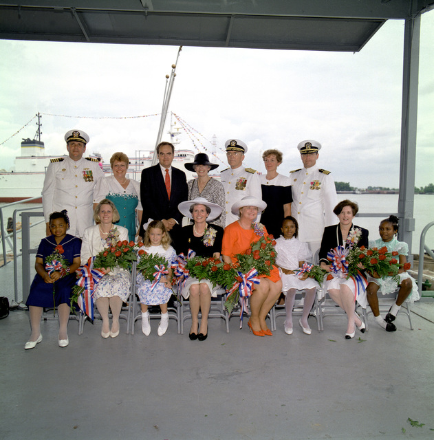 The christening part of the surveying ship USNS WATERS (T-AGS-45) poses for a photograph. Seated, from left to right: flower girl Alicia Bradford, sponsor Ann Waters Scott, flower girl Katie White, sponsor Dabney Waters Schmitt, sponsor Carol Weir Waters, flower girl Keanne Bethencourt, sponsor Martha Waters Philipps, and flower girl Karissa Casey Jackson. Standing from left to right: CAPT and Mrs. John C. Donahue III, Albert L. Bossier, Mrs. and VADM Francis R. Donovan, Mrs and CAPT Ted Doroshenk