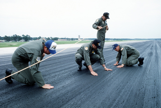 (Left to right) CMSGT Cecil Fultz, MSGT J. B. Rickert, CMSGT Bob Scheid and CMSGT Tom Johnson, RODEO 92 accuracy landing umpires, check the Pope Air Force Base runway for hot rubber from the tires of a competing aircraft and measure from that spot to a predetermined touchdown point