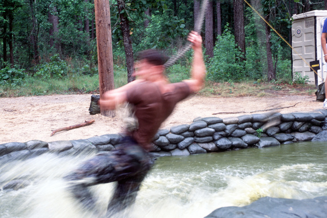 A1C C. Pearson of the 23rd Wing's RODEO 92 team navigates a water filled ditch during the endurance course competition. The 23rd is from Pope Air Force Base
