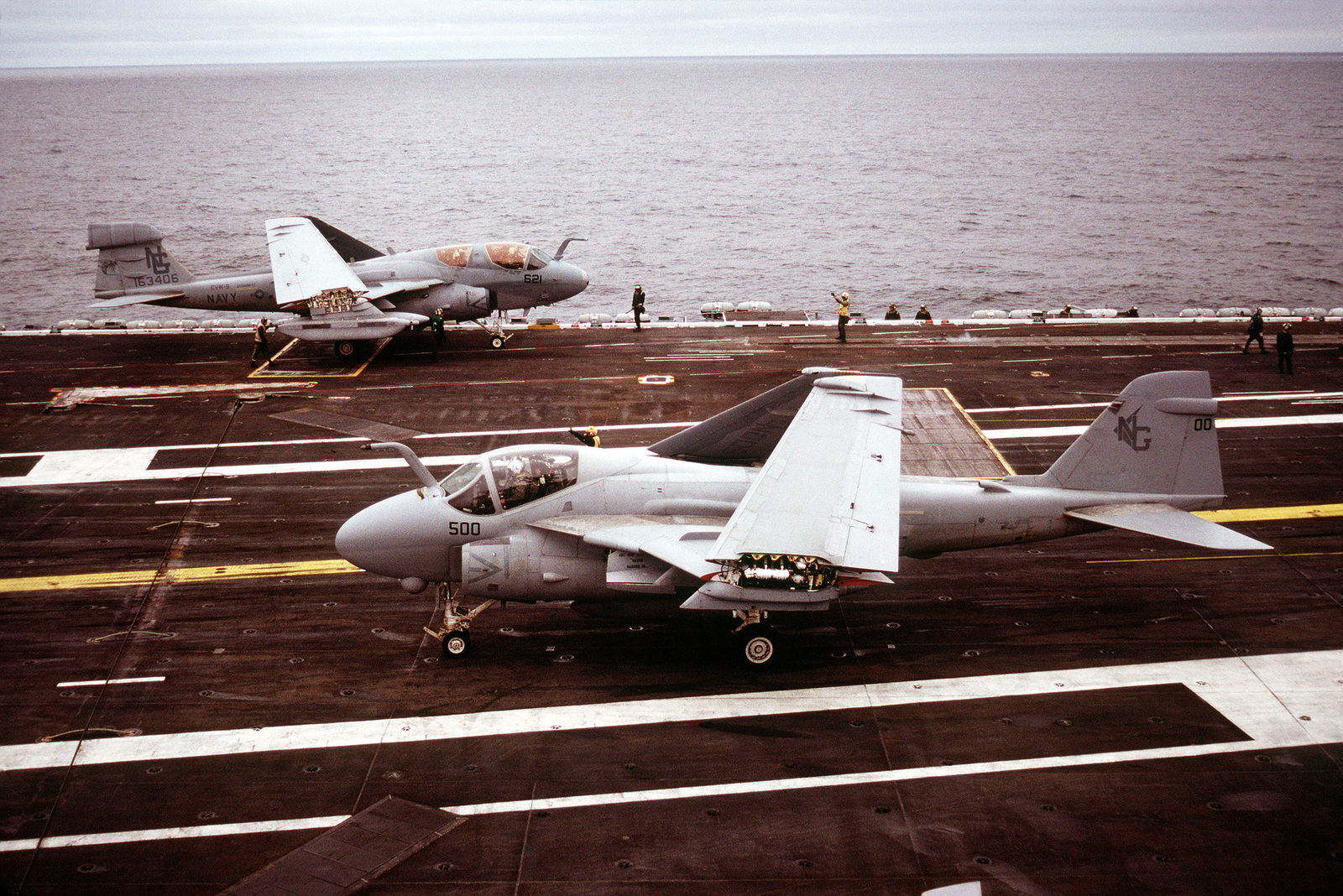 An A-6E Intruder aircraft of Attack Squadron 165 (VA-165) taxis on the flight deck, foreground, as an EA-6B Prowler aircraft, background, of Tactical Electronic Warfare Squadron 138 (VAQ-138) is prepared for launch during flight operations aboard the nuclear-powered aircraft carrier USS NIMITZ (CVN-68)