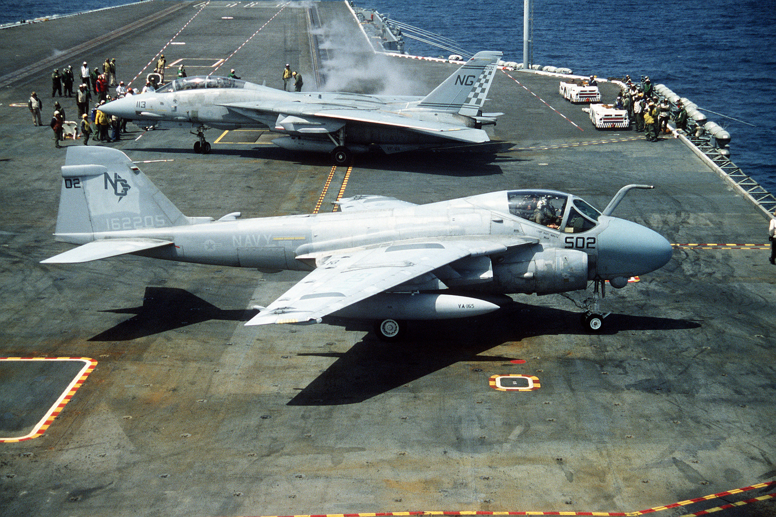 An Attack Squadron 165 (VA-165) A-6E Intruder aircraft, foreground, and a Fighter Squadron 211 (VF-211) F-14A Tomcat aircraft, background, stand by following the launch of another aircraft during flight operations aboard the nuclear-powered aircraft carrier USS NIMITZ (CVN-68)