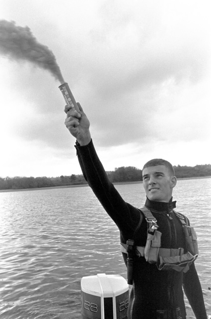 Aviation Anti-submarine Warfare Operator 2nd Class Chad Bruckshen of Helicopter Light Anti-submarine Squadron 94 (HSL-94), Naval Air Station, Willow Grove, Pa., uses a daylight flare to signal and rescue helicopter from a safety boat during search and rescue training at Blue Marsh Lake