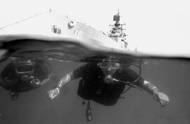 Navy divers CHIEF Quartermaster Terry Miranda and Hull Maintenance Technician 2nd Class Bob Bekesz tread water near the guided missile cruiser USS STERETT (CG-31)