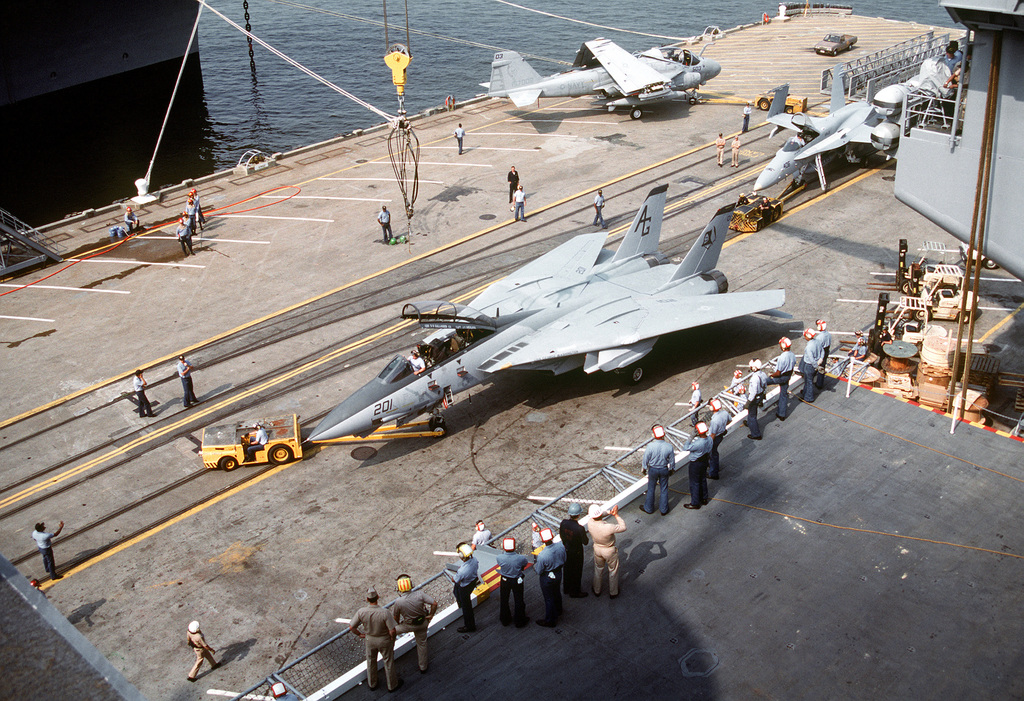 An MD-3A tow tractor positions a Fighter Squadron 142 (VF-142) F-14A Tomcat aircraft on the pier as the plane is readied for lifting by crane onto the nuclear-powered aircraft carrier USS GEORGE WASHINGTON (CVN-73). Aircraft are being lifted aboard the carrier in preparation for the vessel's commissioning ceremony on July 4th