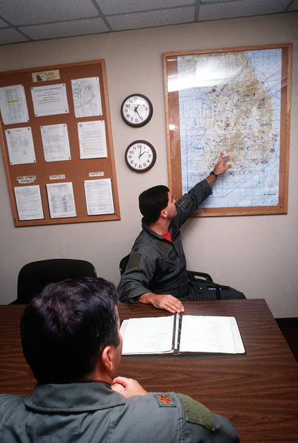 CAPT. Jeff Prichard points to a map of the Republic of Korea while conducting a pre-mission briefing with MAJ. Jeff Fellmeth. Both officers are pilots with the 18th Operations Group, headquartered at Kadena Air Base, Japan