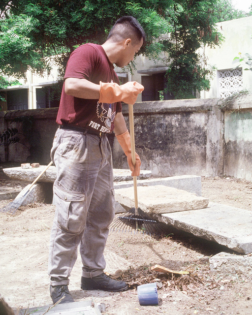 A crew member from the amphibious command ship USS BLUE RIDGE (LCC-19) does yard work at the Little Siters of the Poor Home for the Elderly as part of the community assistance program, Project Handclasp