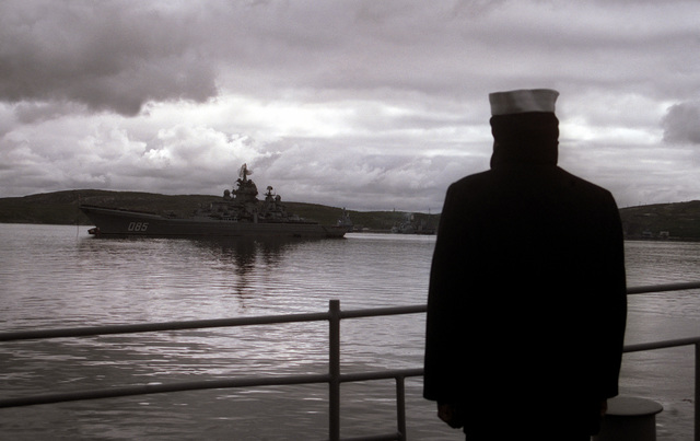 A sailor stands at the railing of the guided missile cruiser USS YORKTOWN (CG-48) as the vessel passes the Russian nuclear-powered guided missile cruiser KALININ upon arriving in port.. The YORKTOWN and the destroyer USS O'BANNON (DD-987) are visiting Severomorsk as part of an ongoing exchange between the navies of the United States and the Commonwealth of Independent States