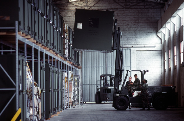 Airmen assigned to the 401st Fighter Wing Logistics Group use a forklift to move containers of war reserve materials in a warehouse