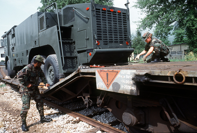 SGT. J.D. Lett, left, and SENIOR AIRMAN Anessa Stoltz, 401st Fighter Wing Logistics Group, remove chocking blocks on a railroad car as they prepare a P-4A aircraft firefighting and rescue truck for unloading. The truck is being prepared for storage as war reserve material