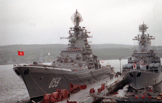 The Russian nuclear-powered guided missile cruiser ADMIRAL USHAKOV, left, still bearing its original name, KIROV, on the gangplank, and the guided missile cruiser MARSHAL USTINOV stand moored to a pier during a port call by two American ships. The Guided missile cruiser USS YORKTOWN (CG-48) and the destroyer USS O'BANNON (DD-987) are visiting Severomorsk as part of an ongoing exchange between the navies of the United States and the Commonwealth of Independent States