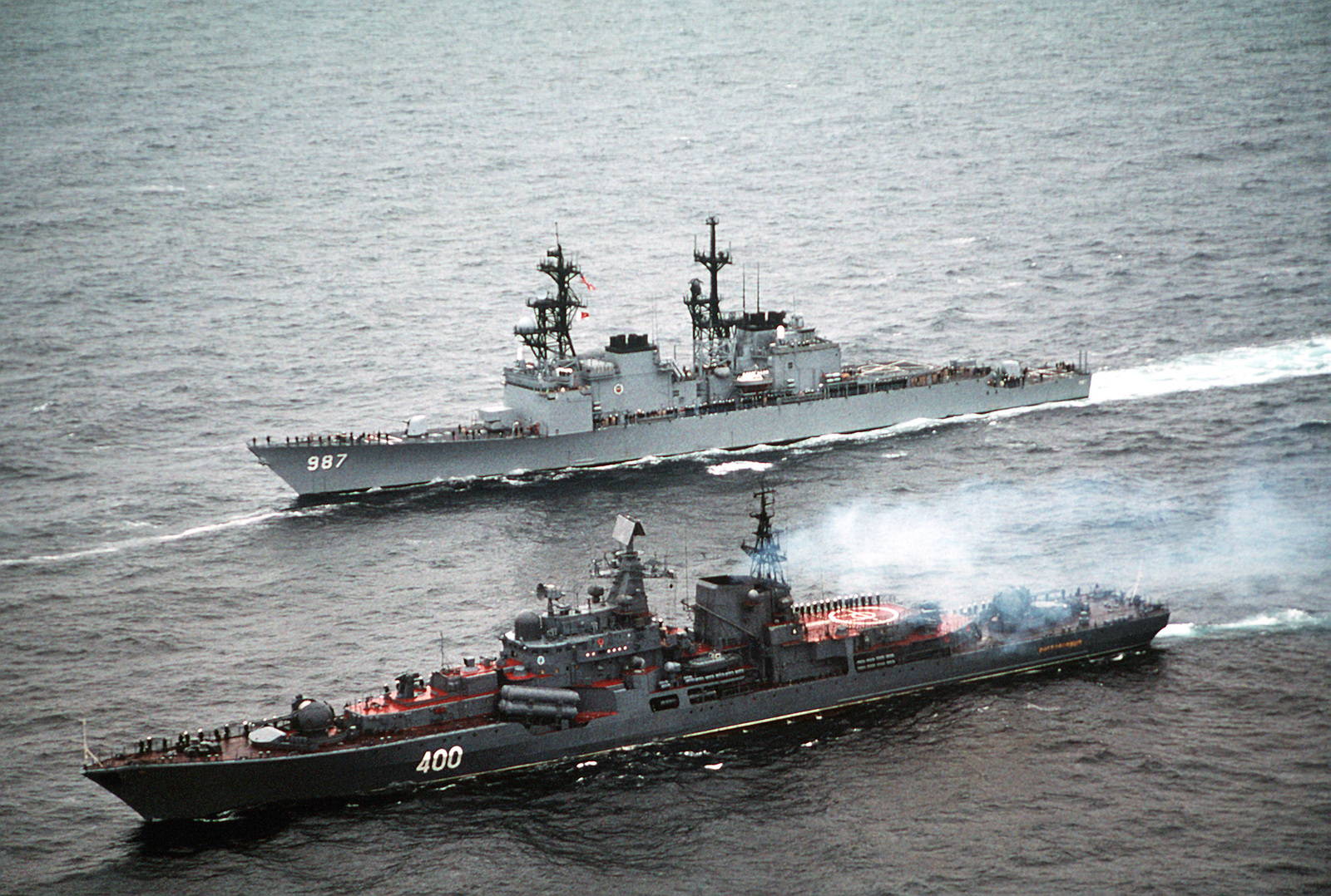 With the crews of both ships manning the rails in the naval tradition of rendering passing honors, the destroyer USS O'BANNON (DD-987) steams alongside the Russian Sovremenny-class destroyer RASTOROPHNNY (EM-400) while heading for the Russian city of Severomorsk