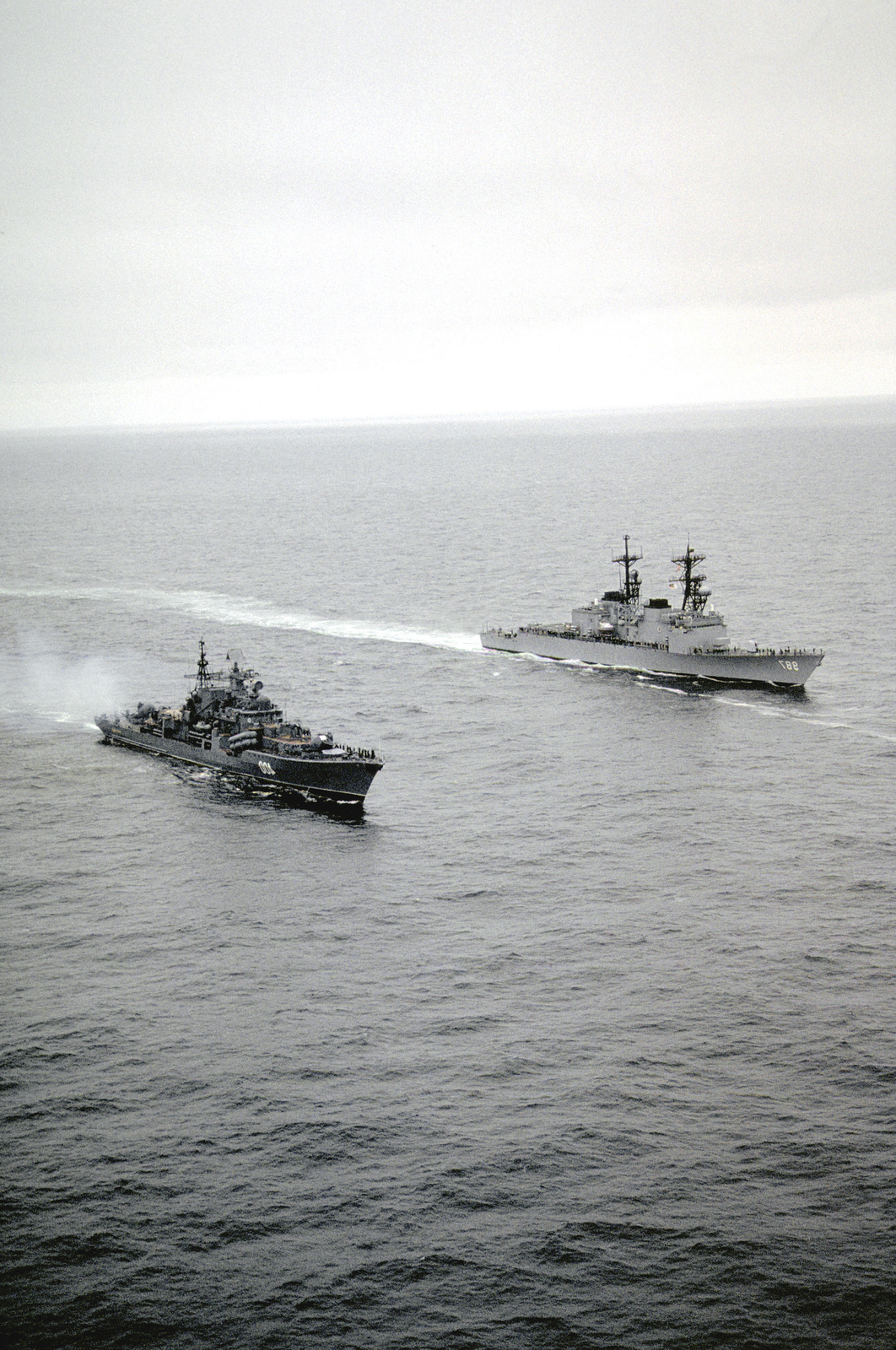 With the crews of both ships manning the rails in the naval tradition of rendering passing honors, the destroyer USS O'BANNON (DD-987) steams alongside the Russian Sovremenny class destroyer RASTOROPNNY (EM-400) while heading for the Russian city of Severomorsk