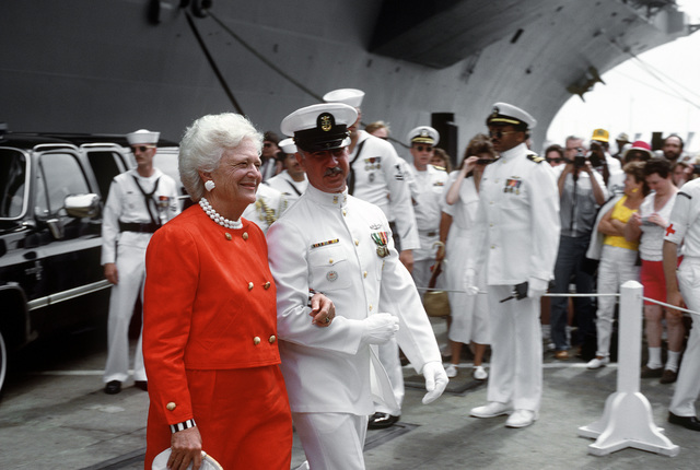 A chief petty officer escorts First Lady Barbara Bush, ship's sponsor, as she arrives for the commissioning ceremony of the nuclear-powered aircraft carrier USS GEORGE WASHINGTON (CVN-73)