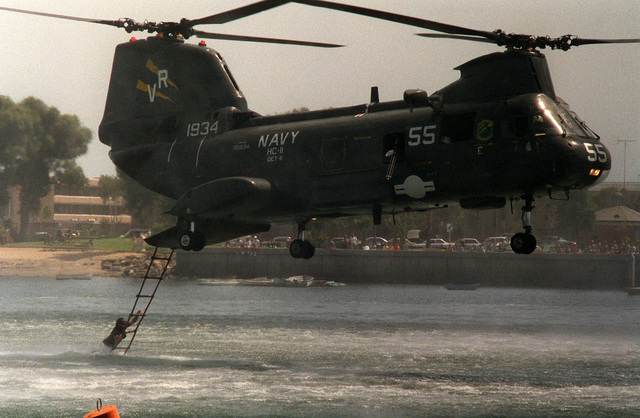 A member of a U.S. Navy Sea-Air-Land (SEAL) team grabs onto a rope ladder to climb into a Helicopter Combat Support Squadron II (HC-11) HH-46D Sea Knight helicopter during a public demonstration