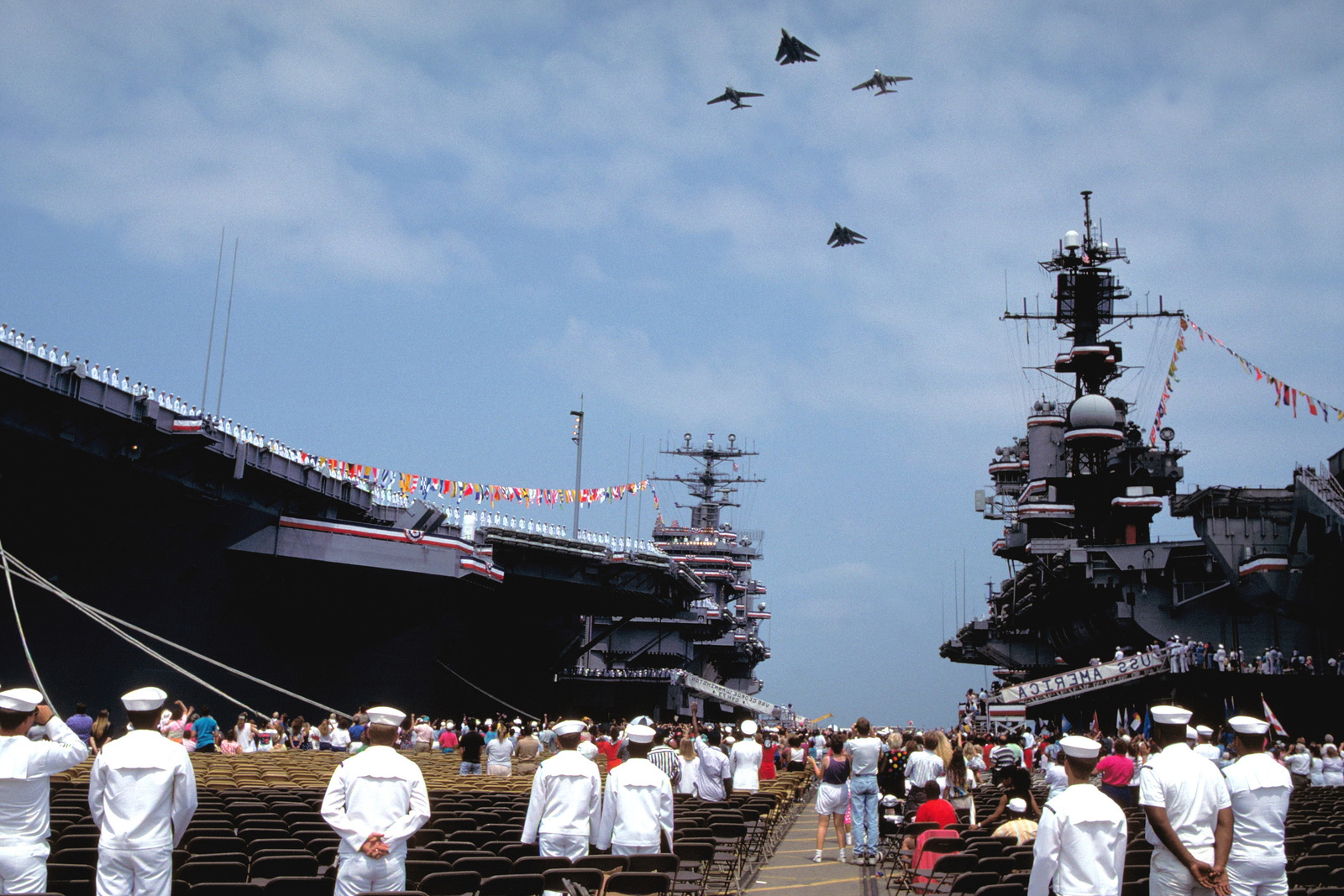 Crew members aboard the nuclear-powered aircraft carrier USS GEORGE WASHINGTON (CVN-73), right, and the aircraft carrier USS AMERICA (CV-66) watch a flyover being conducted in honor of the GEORGE WASHINGTON's commissioning. F-14A Tomcat and A-6E Intruder aircraft are taking part in the flyover