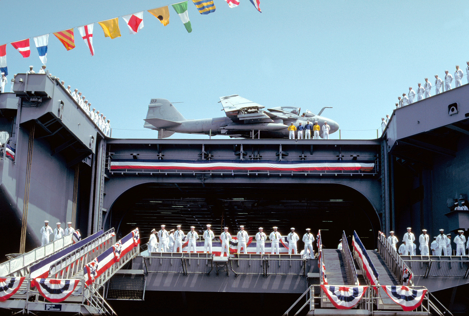 Crew members man the rails aboard the nuclear-powered aircraft carrier USS GEORGE WASHINGTON (CVN-73) during the vessel's commissioning ceremony. An A-6E Intruder aircraft is parked above the hangar bay on the flight deck