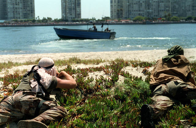 Members of a U.S. Navy Sea-Air-Land (SEAL) team act as the opposing force personnel while other SEALs patrol the waterway during a press demonstration