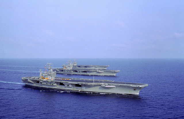 A starboard view of the nuclear-powered aircraft carrier USS GEORGE WASHINGTON (CVN-73) underway in formation with the nuclear-powered aircraft carriers USS THEODORE ROOSEVELT (CVN-71), center, and the USS DWIGHT D. EISENHOWER (CVN-69) during flight deck and catapult certification exercises off the Virginia Capes