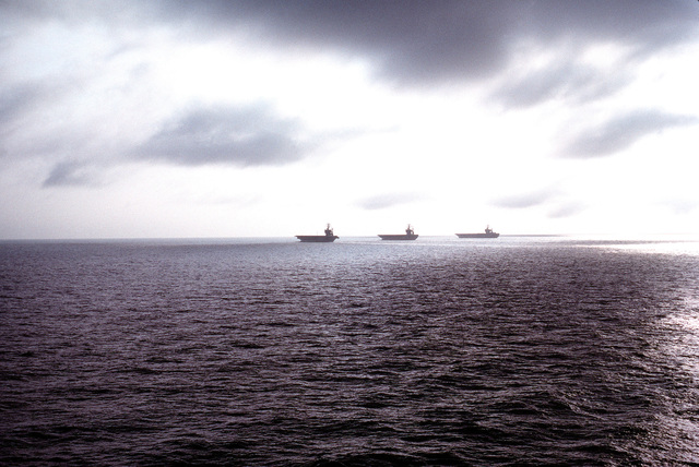 A view of three carriers silhouetted on the horizon while underway in formation during flight deck and catapult certification exercises off the Virginia Capes. The vessels include the nuclear-powered aircraft carrier USS GEORGE WASHINGTON (CVN-73) and the nuclear-powered aircraft carriers USS THEODORE ROOSEVELT (CVN-71) and USS DWIGHT D. EISENHOWER (CVN-69)