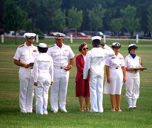RADM Arthur K. Cebrowski and Dr. Joan S. Carver, dean of arts and sciences at Jacksonville University and a member of the Defense Advisory Committee on Women in Service, present awards to graduating members of a co-ed recruit company at Naval Training Center, Orlando. Recruit Training Command, Orlando, is the only Navy command where both men and women undergo basic training