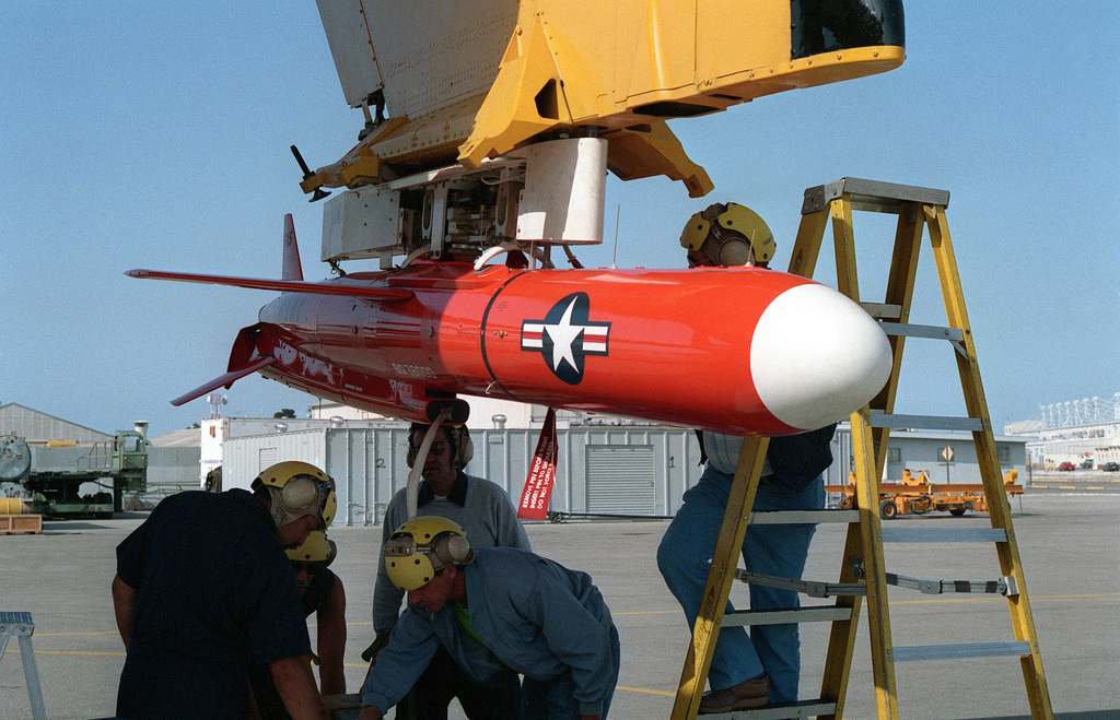 A BQM-74E target drone hangs from a wing pylon of a DC-130A Hercules aircraft. Operational test and evaluation exercises of the drone are being conducted by the Missile Targets Division of the Naval Air Warfare Center Weapons Division