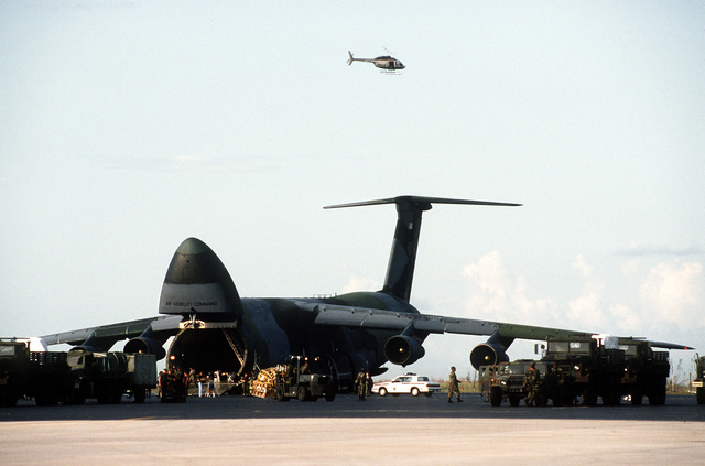A C-5A Galaxy aircraft carrying relief supplies is unloaded on the flight line in the aftermath of Hurricane Andrew, which struck the area on August 24th