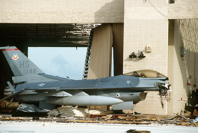 A damaged F-16C Fighting Falcon aircraft stands on the tarmac in the aftermath of Hurricane Andrew, which struck the area on August 24th