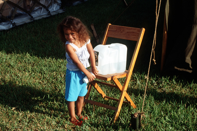 A little girl gets a drink of water at the U.S. Marine Corps Camp Two Life Support Center, a distribution point of supplies for area residents in the aftermath of Hurricane Andrew, which struck the region on August 24th