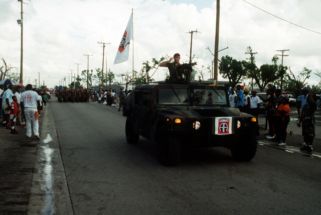 A member of Company D, 4th Battalion, 325th Infantry, 82nd Airborne Division, salutes to onlookers from atop an M998 High-Mobility Multipurpose Wheeled Vehicle (HMMWV) as he and his unit take part in a parade being held in honor of the various military units in the area that assisted with cleanup efforts in the aftermath of Hurricane Andrew, which struck the region on August 24th