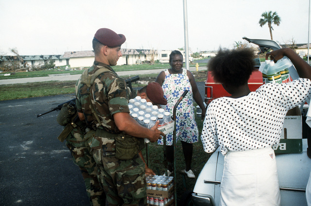 A member of the Army's 82nd Airborne Division loads food supplies for area residents into a car during relief efforts in the aftermath of Hurricane Andrew, which struck the region on August 24th