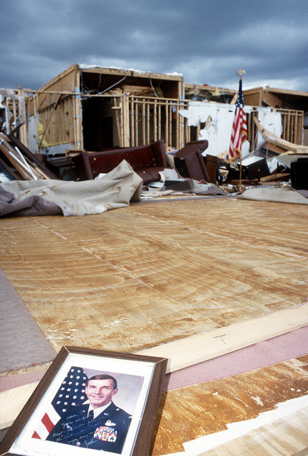 A picture sits in the foreground of destroyed on-base quarters in the aftermath of Hurricane Andrew, which struck the area on August 24th